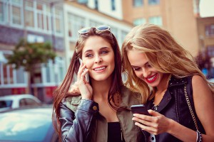 Outdoor portrait of two cheerful young women using smart phones on the street.